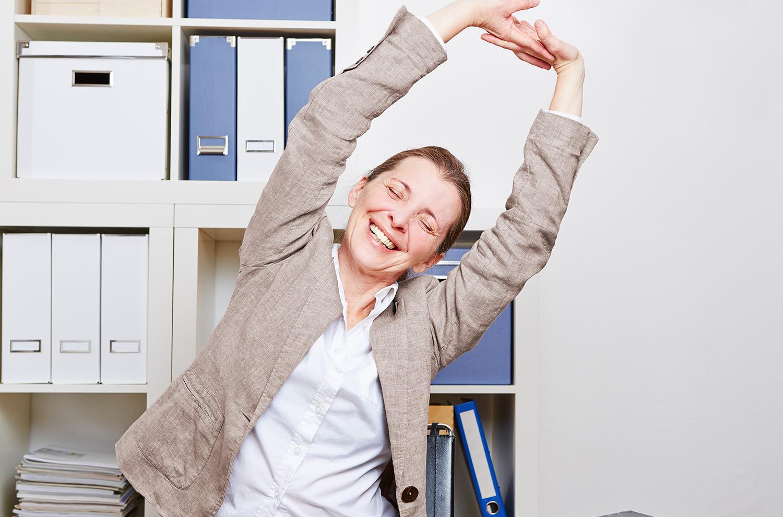 Glad kvinde på arbejde, der strækker sig