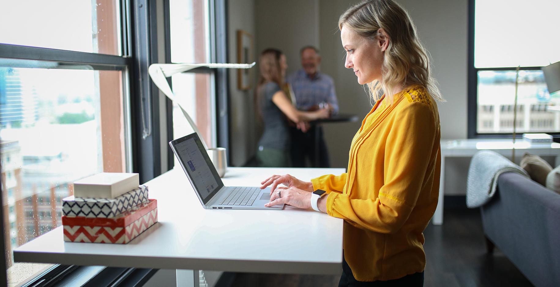 Kvinde står ved skrivebord på arbejde