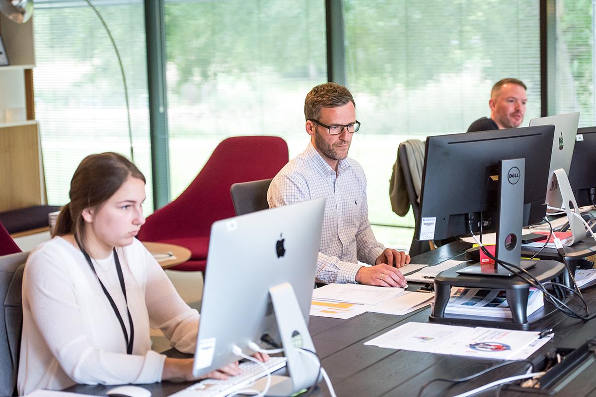 Tre personer sidder ved deres skrivebord og arbejder foran computeren