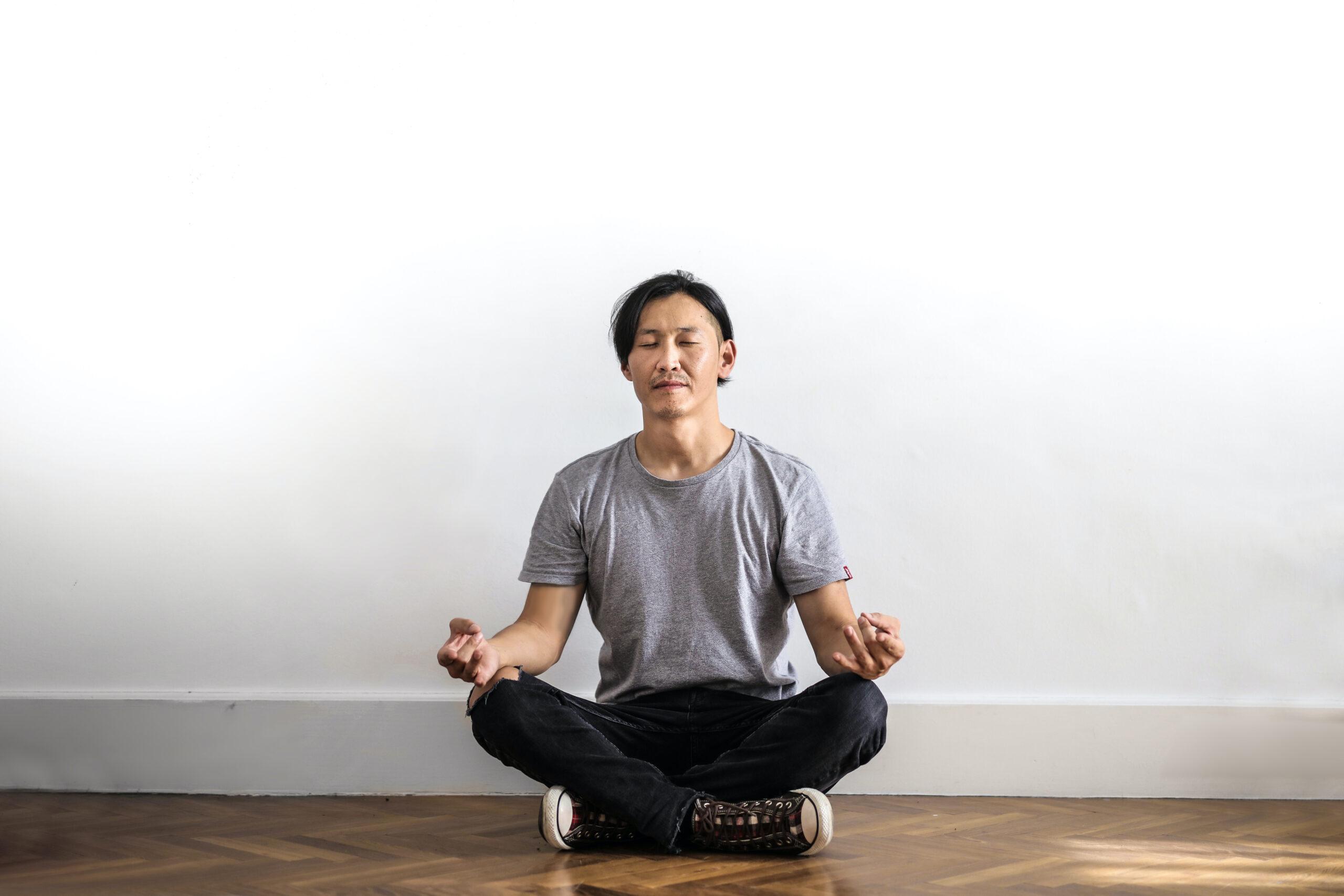 Mand, der mediterer på gulvet